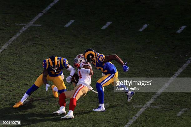 Kendrick Bourne of the San Francisco 49ers is tackled by John Johnson and Trumaine Johnson of the Los Angeles Rams during the second half of a game...