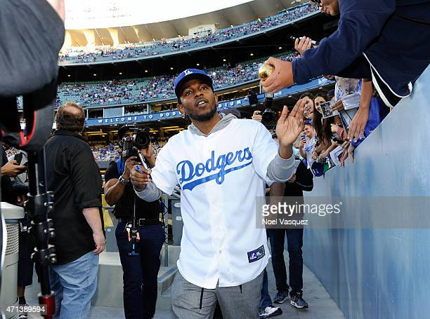 Kendrick Lamar signs autographs before a baseball game between the San Francisco Giants and the Los Angeles Dodgers at Dodger Stadium on April 27...