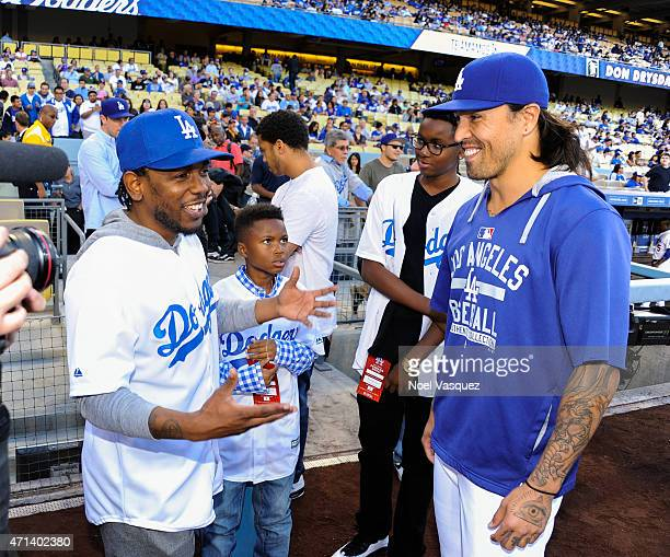 Kendrick Lamar speaks with Brandon League prior to throwing out the ceremonial first pitch at a baseball game between the San Francisco Giants and...