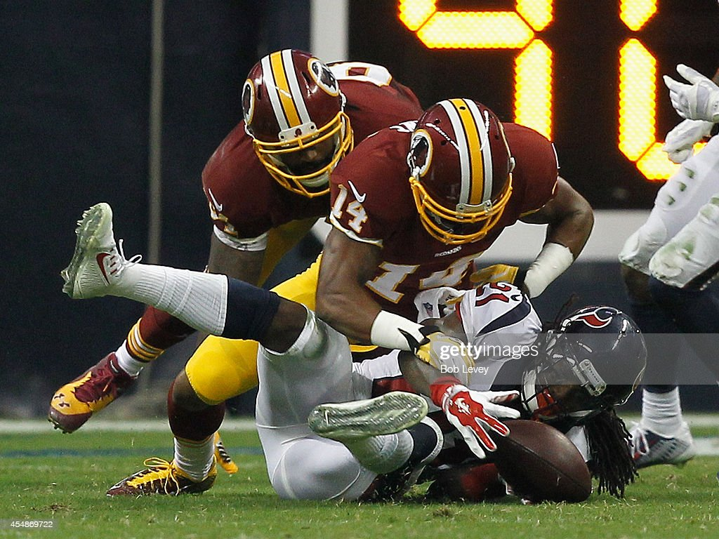 Kendrick Lewis #21 of the Houston Texans recovers a fumble as Ryan Grant #14 of the Washington Redskins attempts to get the ball back in the third quarter at Reliant Stadium on September 7, 2014 in Houston, Texas.