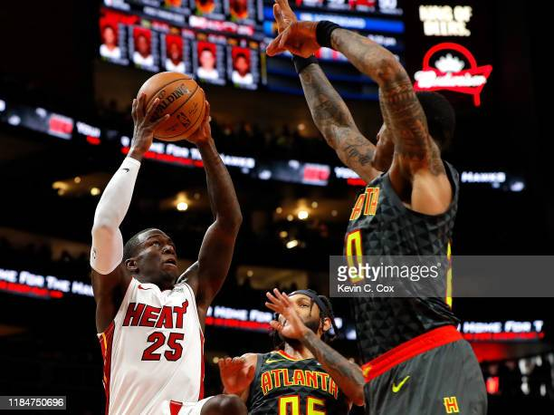 Kendrick Nunn of the Miami Heat drives against John Collins and DeAndre' Bembry of the Atlanta Hawks in the first half at State Farm Arena on October...