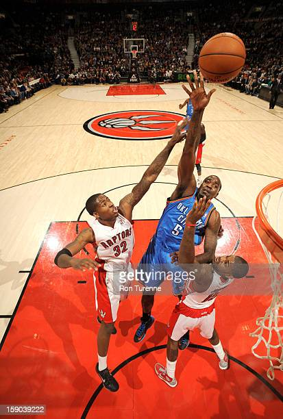 Kendrick Perkins of the Oklahoma City Thunder goes to the basket against Ed Davis of the Toronto Raptors and Amir Johnson of the Toronto Raptors...