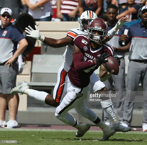 Kendrick Rogers of the Texas AM Aggies attempts to make a catch as Noah Igbinoghene of the Auburn Tigers knocks the ball loose during the first half...