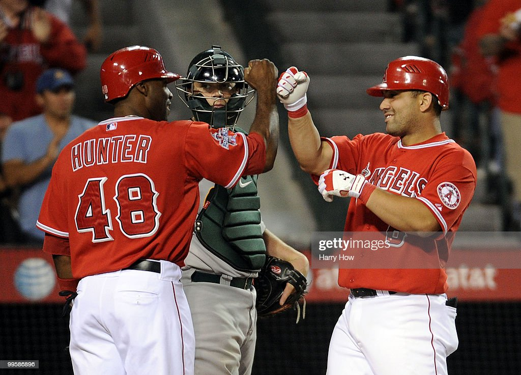 Kendry Morales #8 celebrates his second homerun of the game with Torii Hunter #48 of the Los Angeles Angels in front of Landon Powell #35 of the Oakland Athletics during the seventh inning at Angels Stadium on May 15, 2010 in Anaheim, California.