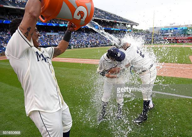 Kendrys Morales of the Kansas City Royals and catching coach Pedro Grifol are doused with water by Salvador Perez as they celebrate a 42 win against...