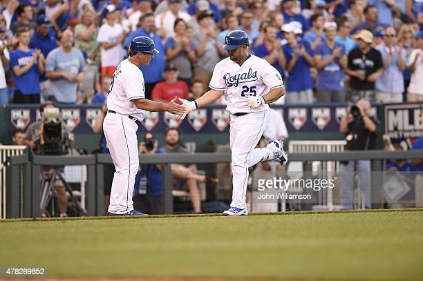 Kendrys Morales of the Kansas City Royals celebrates hitting a home run as he passes third base coach Mike Jirschele while rounding the bases in the...