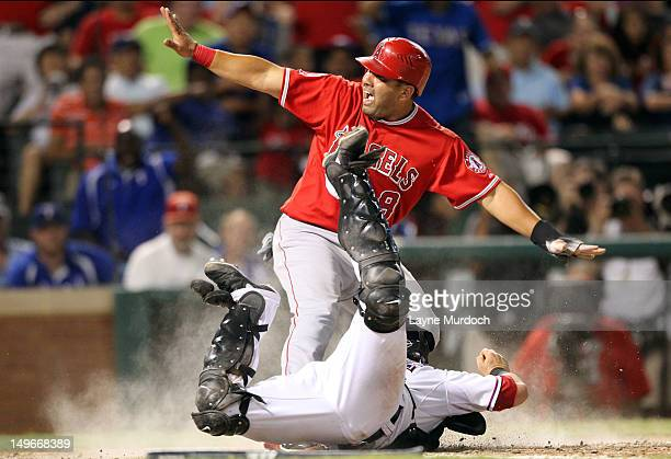 Kendrys Morales of the Los Angeles Angels of Anaheim is tagged out at the plate by Mike Napoli of the Texas Rangers on a throw by Nelson Cruz on...