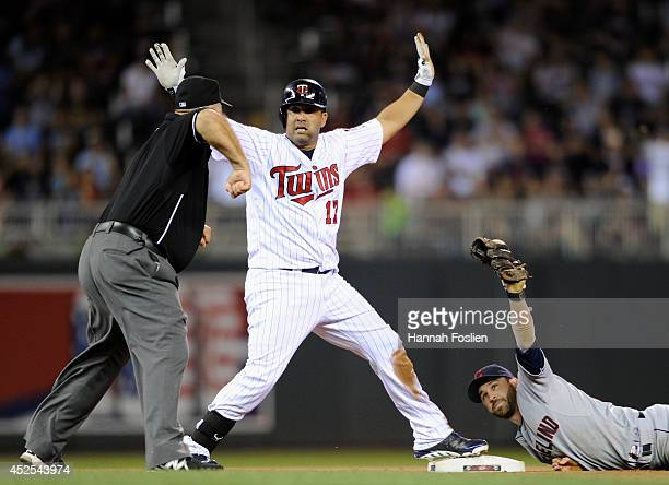 Kendrys Morales of the Minnesota Twins reacts as umpire Brian O'Nora calls him out at second base and Jason Kipnis of the Cleveland Indians shows the...