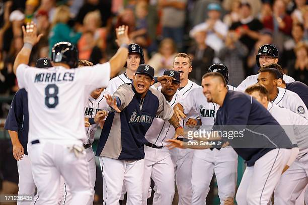 Kendrys Morales of the Seattle Mariners is congratulated by teammates after hitting a walkoff threerun home run in the tenth inning against the...