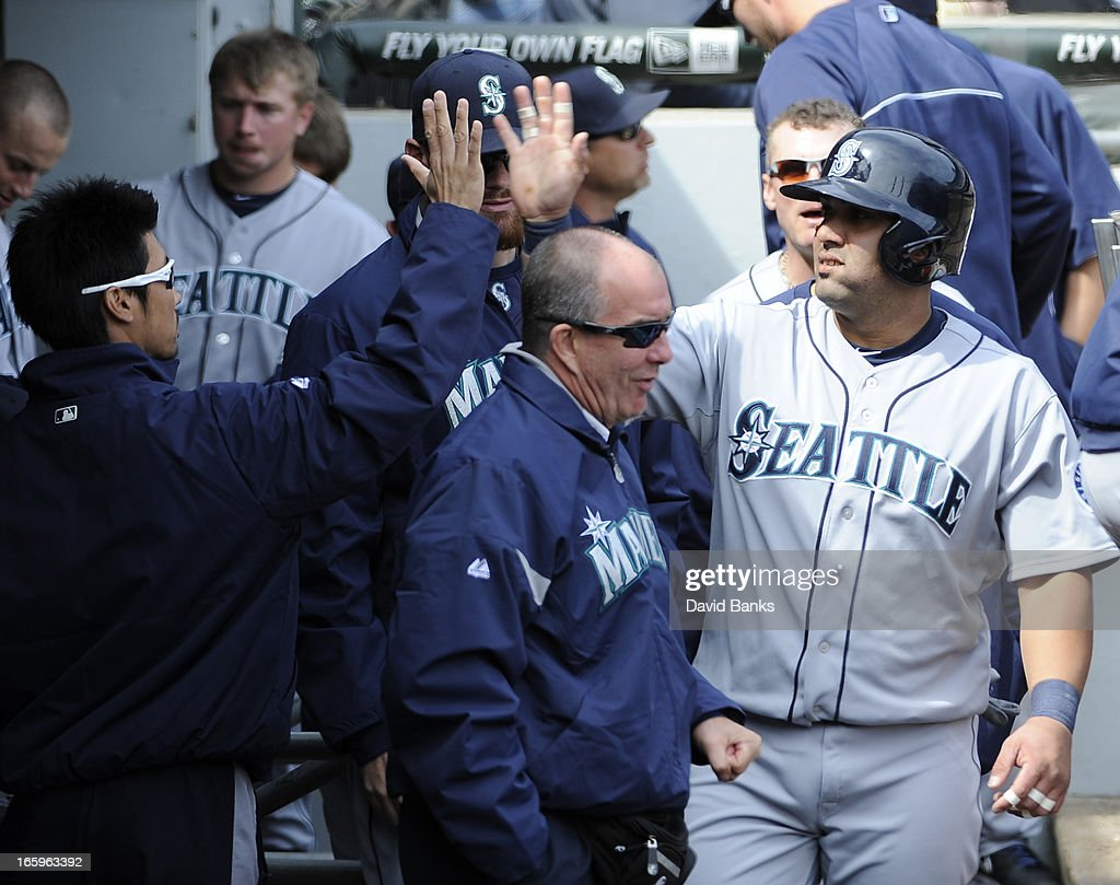 Kendrys Morales (R) of the Seattle Mariners is greeted by teammates after hitting a home-run against the Chicago White Sox in the sixth inning on April 7, 2013 at U.S. Cellular Field in Chicago, Illinois.