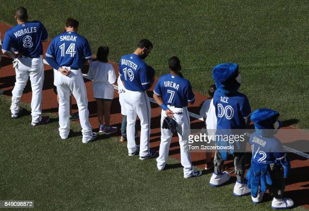 Kendrys Morales of the Toronto Blue Jays and Justin Smoak and Jose Bautista and Richard Urena and mascot Ace stand for the playing of the anthems on...
