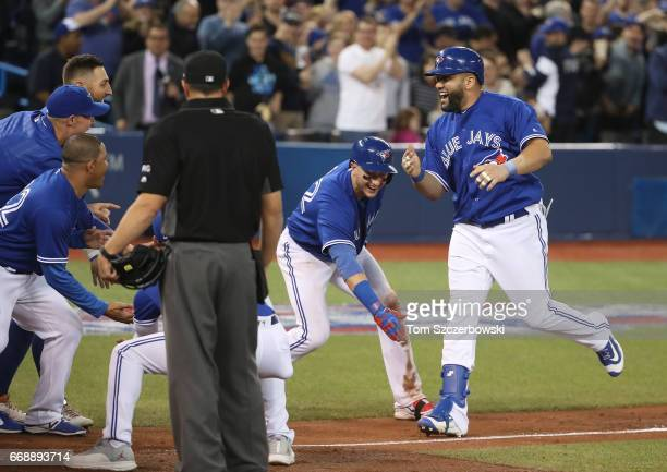 Kendrys Morales of the Toronto Blue Jays is congratulated at home plate by Troy Tulowitzki and teammates after hitting a gamewinning solo home run in...