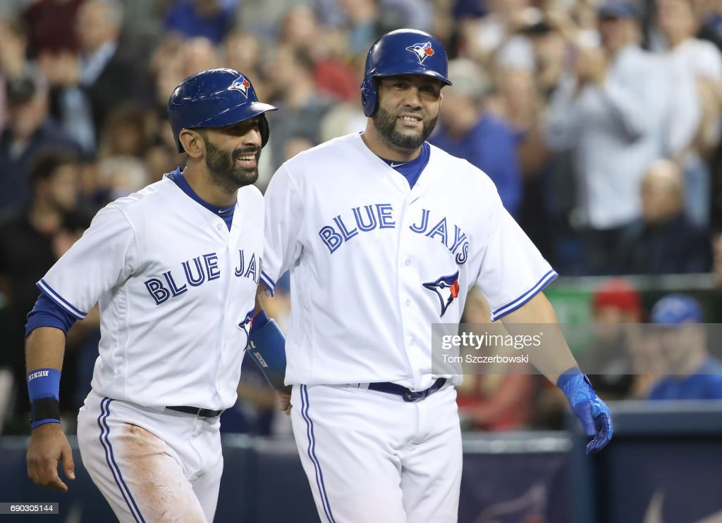 Kendrys Morales #8 (R) of the Toronto Blue Jays is congratulated by Jose Bautista #19 after hitting a two-run home run in the eighth inning during MLB game action against the Cincinnati Reds at Rogers Centre on May 30, 2017 in Toronto, Canada.
