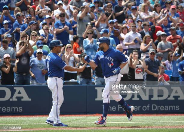 Kendrys Morales of the Toronto Blue Jays is congratulated by third base coach Luis Rivera after hitting a solo home run in the seventh inning during...