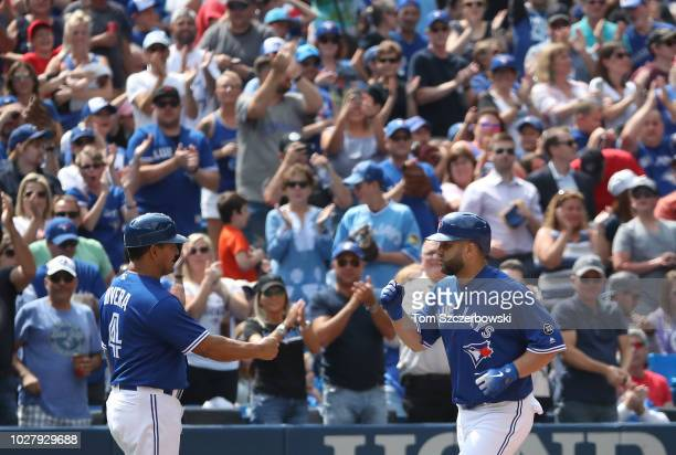 Kendrys Morales of the Toronto Blue Jays is congratulated by third base coach Luis Rivera as he circles the bases after hitting a solo home run in...