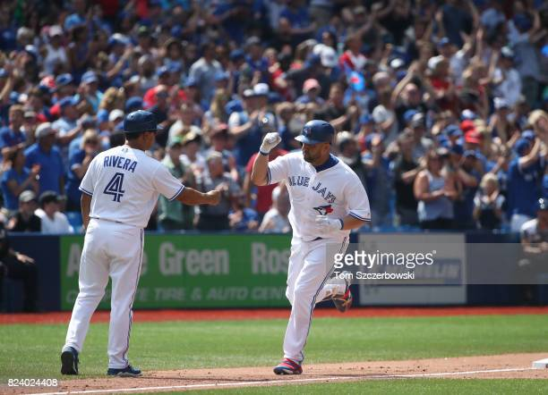 Kendrys Morales of the Toronto Blue Jays is congratulated by third base coach Luis Rivera after hitting a gametying solo home run in the ninth inning...