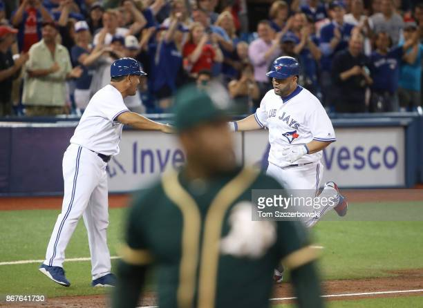 Kendrys Morales of the Toronto Blue Jays is congratulated by third base coach Luis Rivera after hitting a gamewinning solo home run in the ninth...
