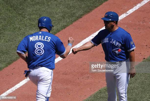 Kendrys Morales of the Toronto Blue Jays is congratulated by third base coach Luis Rivera after hitting a solo home run in the sixth inning during...