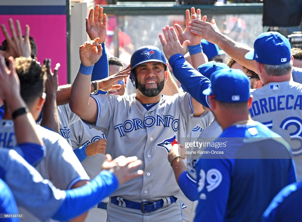 Kendrys Morales #8 of the Toronto Blue Jays is congratulated in the dugout after hitting a go-ahead solo home run in the tenth inning game against the Los Angeles Angels of Anaheim at Angel Stadium on June 24, 2018 in Anaheim, California.