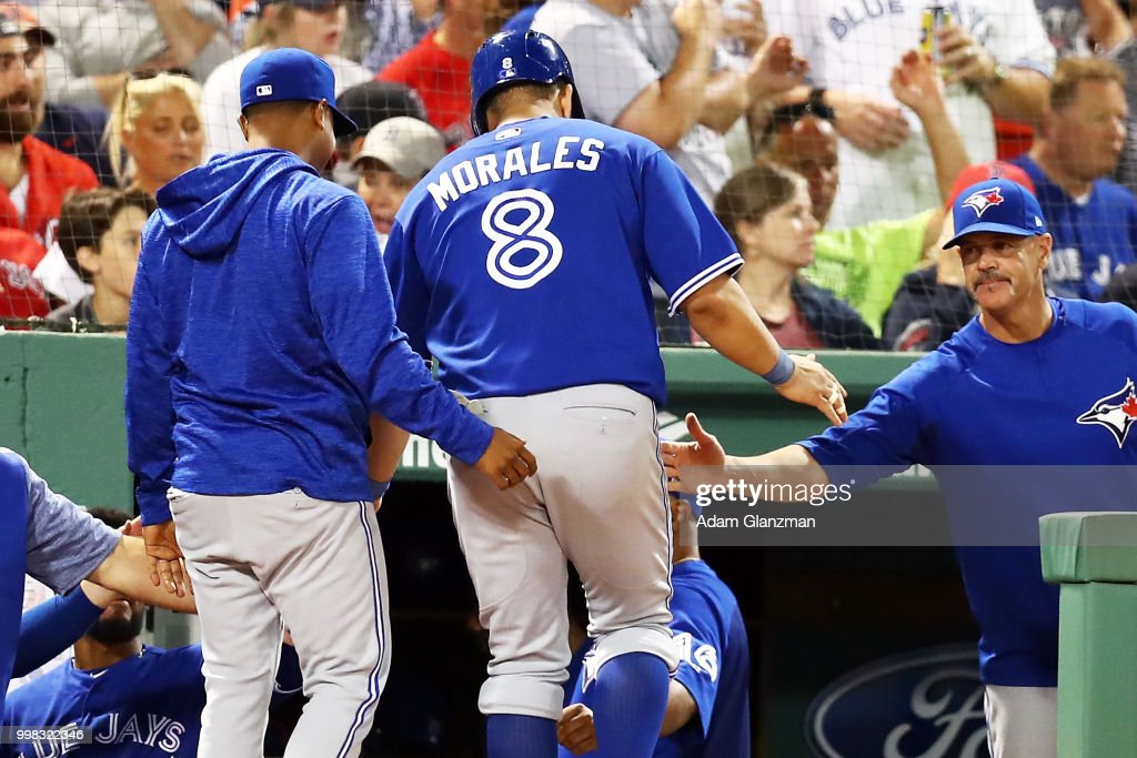 Kendrys Morales #8 of the Toronto Blue Jays return to the dugout after scoring in the eighth inning of a game against the Boston Red Sox at Fenway Park on July 13, 2018 in Boston, Massachusetts.