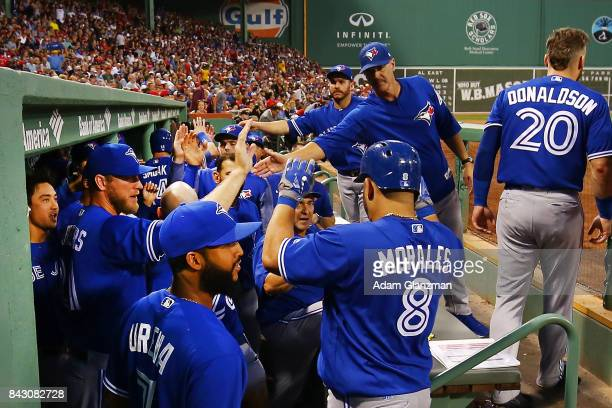 Kendrys Morales of the Toronto Blue Jays returns to the dugout after hitting a threerun home run in the first inning of a game against the Boston Red...
