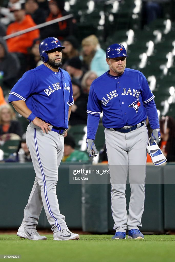 Kendrys Morales #8 of the Toronto Blue Jays talks with first base coach Tim Leiper #34 against the Baltimore Orioles at Oriole Park at Camden Yards on April 9, 2018 in Baltimore, Maryland.