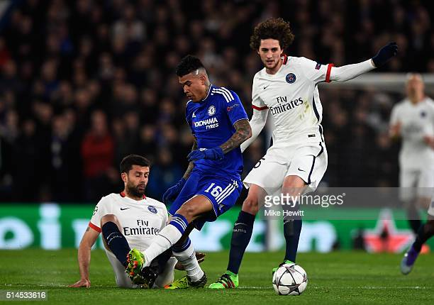Kenedy of Chelsea is tackled by Thiago Motta of PSG and Adrien Rabiot of PSG during the UEFA Champions League round of 16 second leg match between...