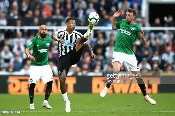 Kenedy of Newcastle United controls the ball while under pressure from Dale Stephens of Brighton and Hove Albion during the Premier League match...