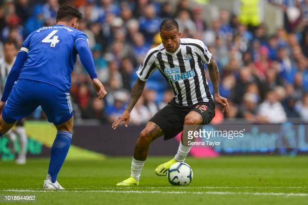 Kenedy of Newcastle United strikes the ball past Sean Morrison of Cardiff City during the Premier League Match between Cardiff City and Newcastle...