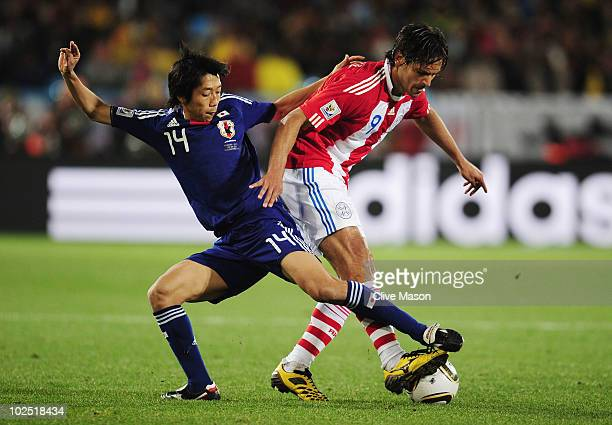 Kengo Nakamura of Japan tackles Roque Santa Cruz of Paraguay during the 2010 FIFA World Cup South Africa Round of Sixteen match between Paraguay and...