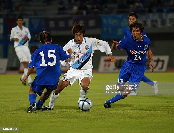Kengo Nakamura of Kawasaki Frontale competes for the ball against Shingo Morita and Yoshio Kitajima of Mito Hollyhock during the JLeague Second...