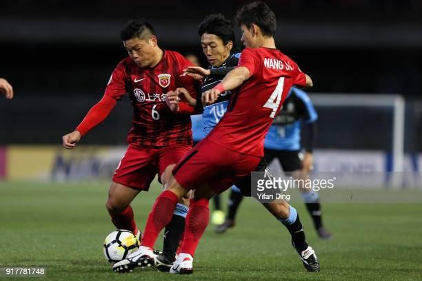 Kengo Nakamura of Kawasaki Frontale dribbles against Cai Huikang and Wang Shenchao of Shanghai SIPG during the AFC Champions League Group F match...
