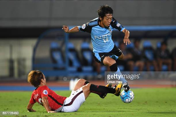 Kengo Nakamura of Kawasaki Frontale is tackled by Shinya Yajima of Urawa Red Diamonds during the AFC Champions League quarter final first leg match...