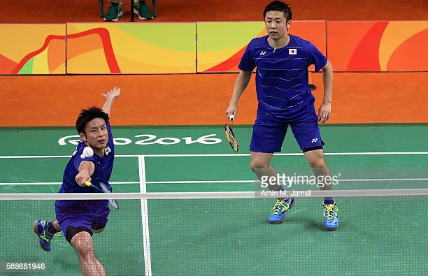 Kenichi Hayakawa and Hiroyuki Endo Of Japan compete against Hendra Setiawan and Mohammad Ahsan of Indonesia in the badminton Men's Doubles Group Play...