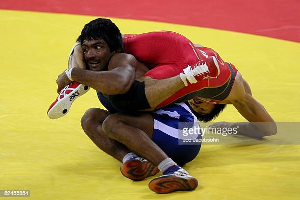 Kenichi Yumoto of Japan competes against Yogeeshwar Dutt of India in the men's 60 kg wrestling event at the China Agriculture University Gymnasium on...