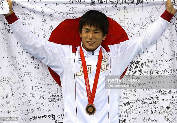 Kenichi Yumoto of Japan holds his countries flag after winning the bronze medal in the men's 60kg freestyle wrestling at the China Agriculture...