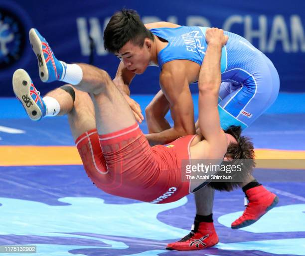 Kenichiro Fumita of Japan throws Victor Ciobanu of Moldova in the Men's GrecoRoman 60kg quarter final on day three of the World Wrestling...