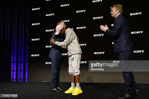 Kenichiro Yoshida president and chief executive officer of Sony Corp left is embraced by Pharrell Williams a singer and performer as Rob Stringer...