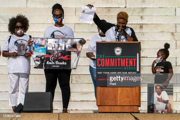 Kenithia Alston, at podium, holds up a document about the 2018 shooting death of her son, Marqueese Alston, by District of Columbia police, next to...