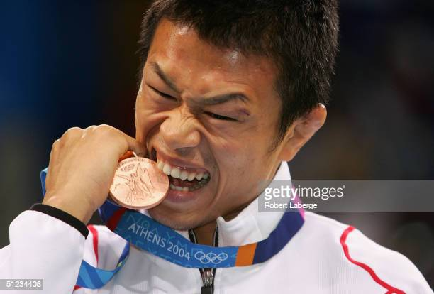 Kenji Inoue of Japan bites his bronze medal after the men's Freestyle wrestling 60 kg bronze medal match on August 29, 2004 during the Athens 2004...