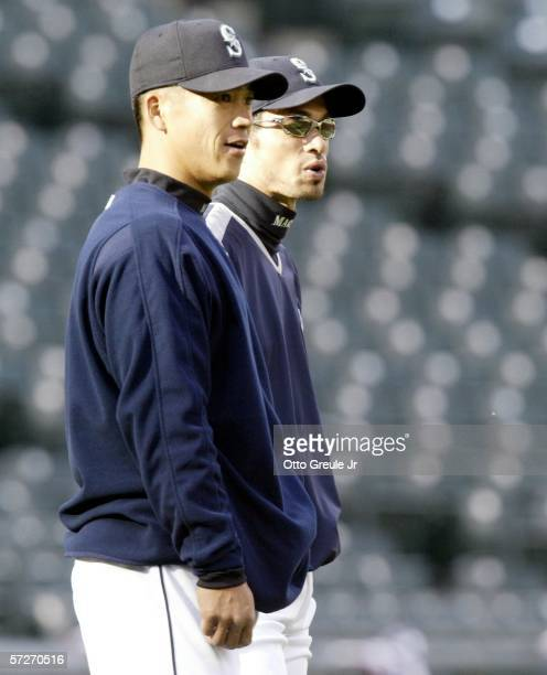 Kenji Johjima and Ichiro Suzuki of the Seattle Mariners watch teammates take batting practice prior to the game against the Oakland A's on April 6,...