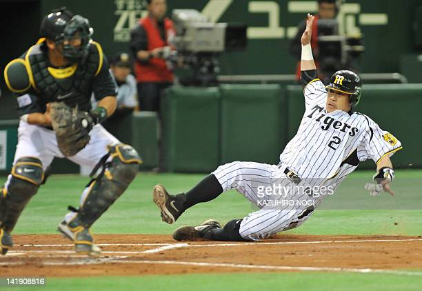 Kenji Johjima of Japan's Hanshin Tigers slides into home past Oakland Athletics catcher Kurt Suzuki during the second inning of their exhibition game...