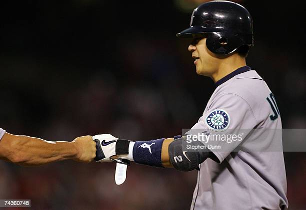 Kenji Johjima of the Seattle Mariners is greeted by first base coach MIke Goff after hitting a single against the Los Angeles Angels of Anaheim on...