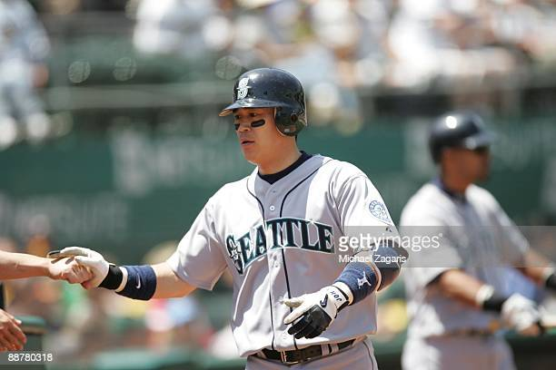 Kenji Johjima of the Seattle Mariners returns to the dugout during the game against the Oakland Athletics at the Oakland Coliseum in Oakland...