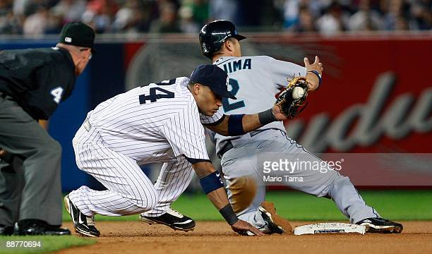 Kenji Johjima of the Seattle Mariners slides safely into second base as Robinson Cano of the New York Yankees applies the tag June 30 2009 at Yankee...