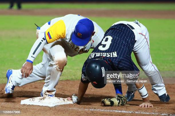 Kenji Nishimaki of Japan returns safely into first base against Jair Camargo of Colombia in the 7th inning during the WBSC U23 World Cup Group A...
