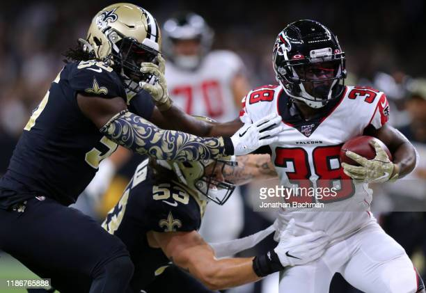 Kenjon Barner of the Atlanta Falcons runs with the ball as Demario Davis of the New Orleans Saints and A.J. Klein defend during the first half of a...