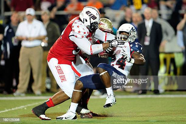 Kenjon Barner of the North squad is brought down by Montori Hughes of the South squad during the Senior Bowl at Ladd Peebles Stadium on January 26...