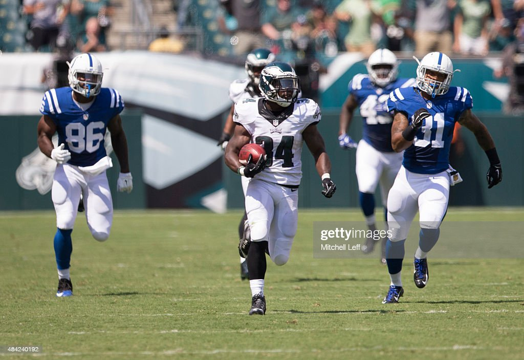 Kenjon Barner #34 of the Philadelphia Eagles runs past Erik Swoope #86 and Dewey McDonald #31 of the Indianapolis Colts on his way to a punt return touchdown on August 16, 2015 at Lincoln Financial Field in Philadelphia, Pennsylvania. The Eagles defeated the Colts 36-10.