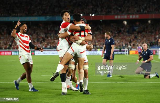 Kenki Fukuoka of Japan celebrates with team mates as he scores their third try as Scotland players Stuart Hogg and Finn Russell react during the...